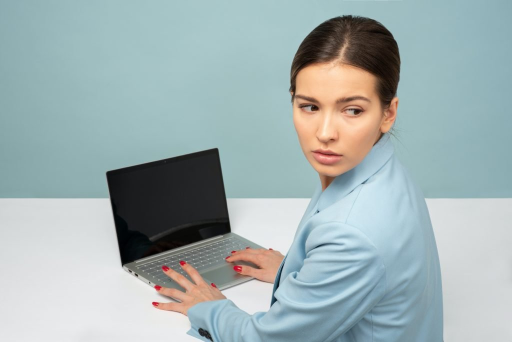 Woman hiding what's on her computer